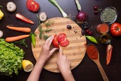 Ανθρώπινα χέρια που κόβουν την ντομάτα στα τέμνοντα λαχανικά πινάκων και παραλλαγής Στοκ Εικόνες