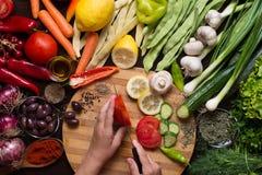 Ανθρώπινα χέρια που τεμαχίζουν τα λαχανικά και την παραλλαγή των λαχανικών και των καρυκευμάτων γύρω Στοκ φωτογραφία με δικαίωμα ελεύθερης χρήσης