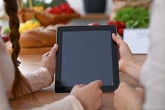 Ανθρώπινα χέρια δύο θηλυκών ατόμων που χρησιμοποιούν touchpad στην κουζίνα Η κινηματογράφηση σε πρώτο πλάνο δύο γυναικών κάνει on Στοκ εικόνες με δικαίωμα ελεύθερης χρήσης