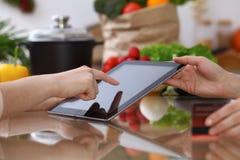 Ανθρώπινα χέρια δύο θηλυκών ατόμων που χρησιμοποιούν touchpad στην κουζίνα Η κινηματογράφηση σε πρώτο πλάνο δύο γυναικών κάνει on Στοκ εικόνα με δικαίωμα ελεύθερης χρήσης