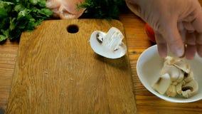 Ανθρώπινα champignon περικοπών χεριών μανιτάρια στα κομμάτια σε έναν ξύλινο πίνακα κουζινών φιλμ μικρού μήκους