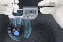 Ανθρώπινη μέτρηση μικρόμετρου χρήσης ψηφιακή ένας κόκκινος έλεγχος σφαιρών στοκ εικόνες με δικαίωμα ελεύθερης χρήσης