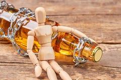 Ανθρώπινη ξύλινη πλαστή συνεδρίαση με το μπουκάλι στοκ εικόνα