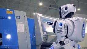 Ανθρώπινος-όπως το ρομπότ έρχεται σε έναν πίνακα ελέγχου και θέτοντας παραμέτρους σε μια οθόνη απόθεμα βίντεο