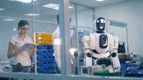Ανθρώπινος-όπως το ρομπότ αντιγράφει τις κινήσεις ενός εργαζομένου εργαστηρίων αρσενικών κάτω από τη επίβλεψη απόθεμα βίντεο