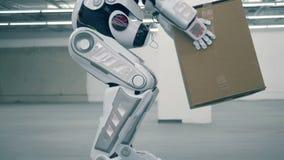 Ανθρώπινος-όπως το ρομπότ ανυψώνει ένα κιβώτιο και το φέρνει φιλμ μικρού μήκους