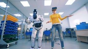 Ανθρώπινος-όπως το ρομπότ και μια νέα γυναίκα στα εικονικά γυαλιά χορεύει απόθεμα βίντεο