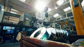 Ανθρώπινος-όπως το ρομπότ με μια ταμπλέτα παρατηρεί τα μέρη μετάλλων φιλμ μικρού μήκους