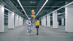 Ανθρώπινος-όπως cyborg και μια γυναίκα κρατά τα μπαλόνια απόθεμα βίντεο