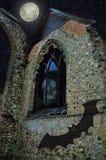 Ανθρώπινο κρανίο στο απόκοσμο αρχαίο παράθυρο κάστρων πέρα από τη πανσέληνο σημειώσεις σεληνόφωτου αποκριών ροπάλων ανασκόπησης Στοκ Εικόνες
