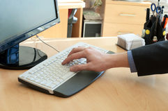 Ανθρώπινο χέρι επάνω σε ένα άσπρο πληκτρολόγιο. Δακτυλογράφηση Στοκ Φωτογραφία