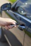 Ανθρώπινο χέρι με έναν τηλεχειρισμό συναγερμών αυτοκινήτων Στοκ φωτογραφία με δικαίωμα ελεύθερης χρήσης