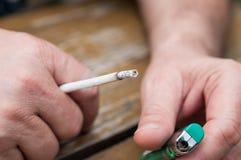 Ανθρώπινο χέρι με ένα τσιγάρο σε ένα χέρι και ένα φως Στοκ φωτογραφία με δικαίωμα ελεύθερης χρήσης