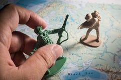 Ανθρώπινο χέρι με τα παιχνίδια στρατιωτών στο χάρτη Στοκ φωτογραφία με δικαίωμα ελεύθερης χρήσης