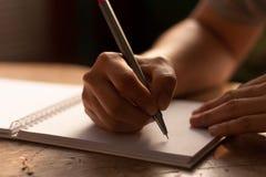 Ανθρώπινο χέρι με τη μάνδρα που γράφει στο σημειωματάριο που ευθυγραμμίζει στο θόριο Στοκ Φωτογραφία