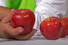 Ανθρώπινο χέρι με το κόκκινο μήλο Στοκ φωτογραφία με δικαίωμα ελεύθερης χρήσης