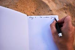 Ανθρώπινο χέρι που κρατά μια μάνδρα και που γράφει τις σημειώσεις σε ένα ημερολόγιο περιοδικών ταξιδιού στην άμμο στη Λευκή Βίβλο Στοκ φωτογραφία με δικαίωμα ελεύθερης χρήσης