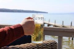 Ανθρώπινο χέρι που κρατά την κούπα μπύρας με το υπόβαθρο λιμνών Στοκ Εικόνες