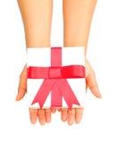 Ανθρώπινο χέρι που κρατά το κόκκινο δώρο τόξων Στοκ εικόνα με δικαίωμα ελεύθερης χρήσης