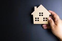Ανθρώπινο χέρι που κρατά το ξύλινο παιχνίδι σπιτιών στο μαύρο υπόβαθρο με τη σπόλα Στοκ Φωτογραφίες