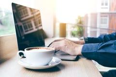 Ανθρώπινο χέρι που λειτουργεί στο lap-top πληκτρολογίων με τον καφέ το πρωί Στοκ Εικόνες