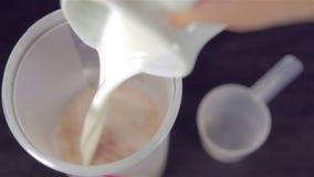 Ανθρώπινο χέρι που πετά μια σέσουλα της πρωτεΐνης ορρού γάλακτος σοκολάτας φιλμ μικρού μήκους