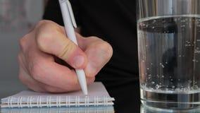 Ανθρώπινο χέρι που χρησιμοποιεί μια μάνδρα σφαιρών για να γράψει κάτι σε ένα σημειωματάριο φιλμ μικρού μήκους