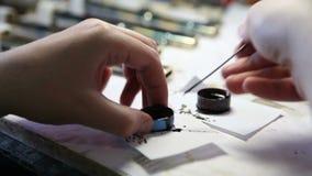 Ανθρώπινο χέρι προμηθειών βουρτσών και ζωγραφικής που αναμιγνύει το μαύρο μελάνι απόθεμα βίντεο