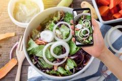 Ανθρώπινο smartphone λαβής χεριών, ταμπλέτα, τηλέφωνο κυττάρων στη μουτζουρωμένη κουζίνα Στοκ εικόνα με δικαίωμα ελεύθερης χρήσης