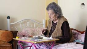 ανθυγειινή ηλικιωμένη γυναίκα που τρώει το χέρι τινάγματος απόθεμα βίντεο