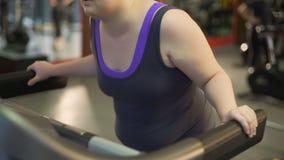 Ανθυγειινή υπέρβαρη γυναίκα που εξαντλείται με την άσκηση treadmill, που περπατά αργά φιλμ μικρού μήκους