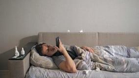 Ανθυγειινό άτομο στο κρεβάτι δίπλα στα φάρμακά του στο σπίτι του που καλεί το τηλέφωνο απόθεμα βίντεο