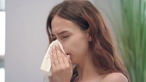 Ανθυγειινό νέο κορίτσι με τη runny μύτη ενώ κρύα ασθένεια που φτερνίζεται στο χαρτομάνδηλο φιλμ μικρού μήκους