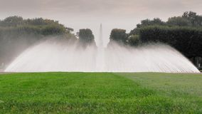 Αννόβερο, Γερμανία Μεγάλη πηγή στον κήπο με το ράντισμα του νερού Στο πρώτο πλάνο ένας πράσινος χορτοτάπητας με τη χλόη r απόθεμα βίντεο