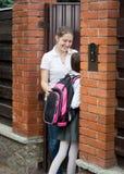 Ανοίγοντας πόρτα μητέρων χαμόγελου όμορφη στην κόρη της που πηγαίνει από Στοκ Φωτογραφία