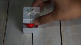 Ανοίγοντας το άσπρο κιβώτιο δώρων με την κόκκινη καρδιά μέσα πέρα από το άσπρο ξύλινο υπόβαθρο απόθεμα βίντεο