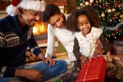 Ανοίγοντας χριστουγεννιάτικο δώρο μικρών κοριτσιών Afro αμερικανικό στοκ φωτογραφία
