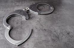 Ανοιγμένες χειροπέδες αστυνομίας στο τραχύ γκρίζο υπόβαθρο με το διάστημα αντιγράφων στοκ εικόνες
