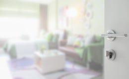 Ανοιγμένη άσπρη πόρτα στη ζωηρόχρωμη κρεβατοκάμαρα με τον καφετή καναπέ ως υπόβαθρο Στοκ εικόνα με δικαίωμα ελεύθερης χρήσης