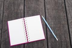 Ανοιγμένη άσπρη σελίδα του κενού ρεαλιστικού σπειροειδούς σημειωματάριου σημειωματάριων και του μπλε μολυβιού στο ξύλινο υπόβαθρο Στοκ Εικόνες
