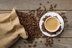 Ανοιγμένη τσάντα καφέ με τα φασόλια και το άσπρο φλυτζάνι του coffe Στοκ Εικόνα