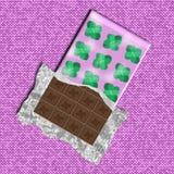 Ανοιγμένος φραγμός σοκολάτας με τα φύλλα μεντών στη συσκευασία που βρίσκεται στο ρόδινο ύφασμα Στοκ φωτογραφίες με δικαίωμα ελεύθερης χρήσης