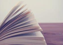 Ανοιγμένο βιβλίο, που βρίσκεται σε ένα ξύλινο υπόβαθρο Στοκ εικόνες με δικαίωμα ελεύθερης χρήσης