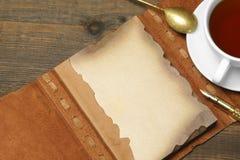 Ανοιγμένο εκλεκτής ποιότητας σημειωματάριο με την κενή καφετιά σελίδα, μάνδρα, φλυτζάνα τσαγιού, Spoo Στοκ Εικόνες
