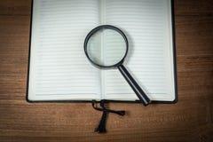 Ανοιγμένο κενό σημειωματάριο με την ενίσχυση - γυαλί Στοκ φωτογραφία με δικαίωμα ελεύθερης χρήσης