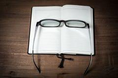 Ανοιγμένο κενό σημειωματάριο με eyeglass σε ξύλινο Στοκ φωτογραφία με δικαίωμα ελεύθερης χρήσης