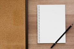 Ανοιγμένο κενό σπειροειδές δεσμευτικό σημειωματάριο δαχτυλιδιών με έναν πίνακα μολυβιών και φελλού στην ξύλινη επιφάνεια Στοκ Εικόνες