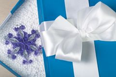Ανοιγμένο μπλε κιβώτιο με το άσπρο τόξο στην κορυφή του Όμορφο έγγραφο snowf Στοκ φωτογραφία με δικαίωμα ελεύθερης χρήσης