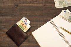 Ανοιγμένο σπειροειδές σημειωματάριο, πορτοφόλι με τα ευρο- μετρητά, μάνδρα στο ξύλο Στοκ Φωτογραφίες