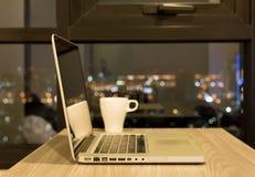 Ανοιγμένο lap-top στον ξύλινο πίνακα με το φλιτζάνι του καφέ τη νύχτα Στοκ φωτογραφίες με δικαίωμα ελεύθερης χρήσης